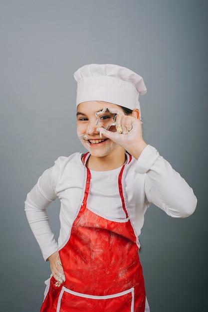 Une Petite Fille En Chapeau De Cuisinier Prépare Le Dîner