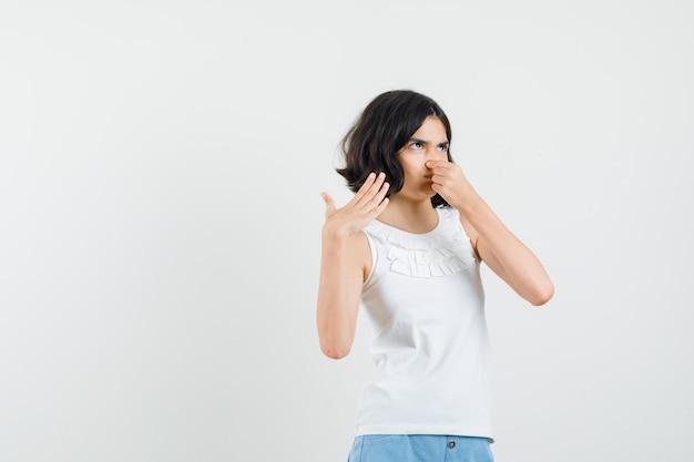 Petite Fille En Chemisier Blanc, Short Pinçant Le Nez En Raison D'une Mauvaise Odeur Et à La Dégoûté, Vue De Face. Photo gratuit