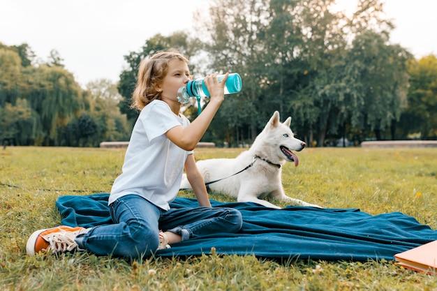 Petite fille avec un chien blanc dans le parc, assis sur l'herbe Photo Premium