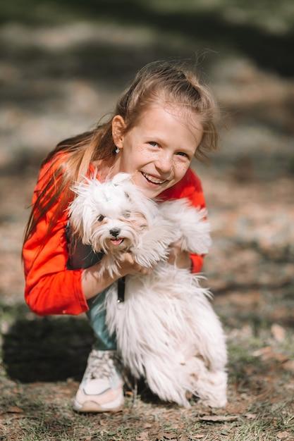 Petite fille avec un chiot blanc, un chiot dans les mains d'une fille Photo Premium