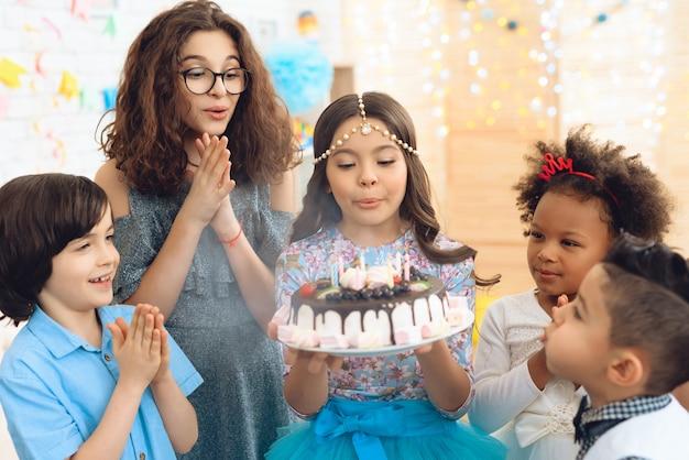 Petite fille coiffée souffle des bougies Photo Premium