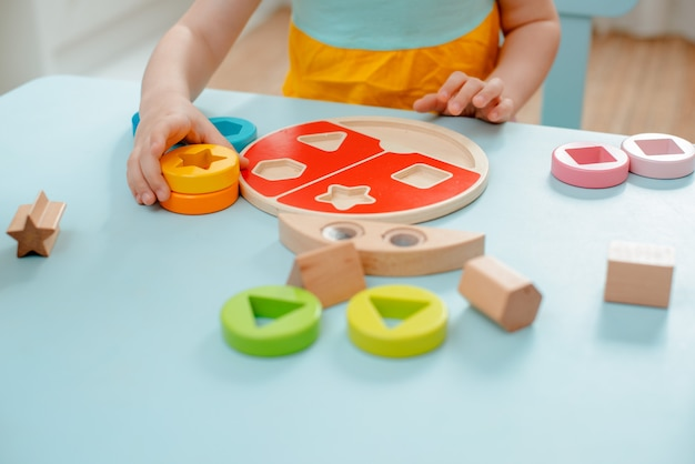 Une petite fille collectionne une trieuse multicolore en bois Photo Premium