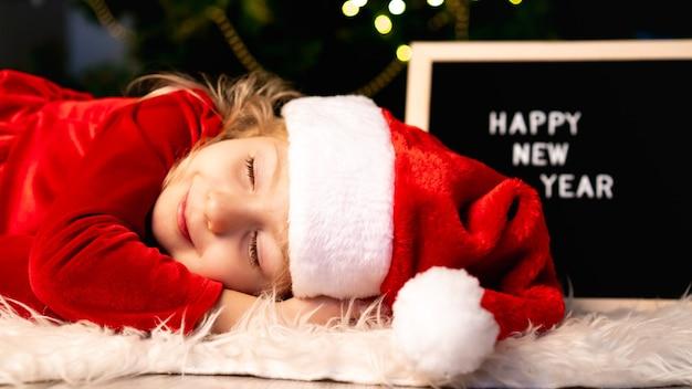 Une Petite Fille En Costume De Noël Et Chapeau De Père Noël Dort Sous L'arbre En Attendant Un Miracle. Photo Premium
