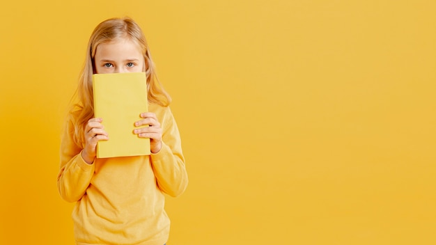 Petite Fille Couvrant Son Visage Avec Livre Photo gratuit