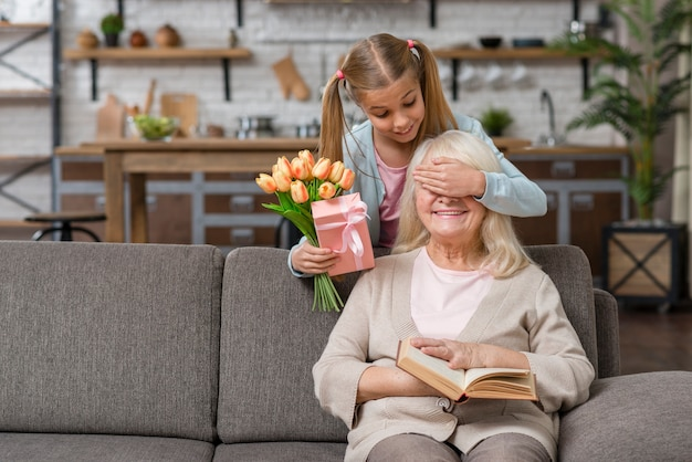 Petite-fille Couvrant Les Yeux De Sa Grand-mère Photo gratuit