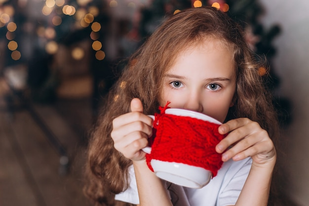 Petite Fille Dans La Décoration De Noël Avec Du Thé à La Maison Confortable Avec Des Lumières Colorées Du Nouvel An Photo Premium
