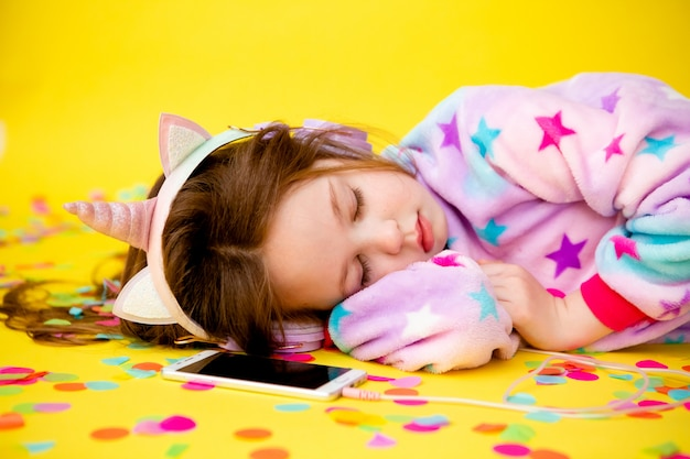 Petite Fille Dans Un Kigurumi Licorne Bénéficie De Confettis Sur Fond Jaune Photo Premium