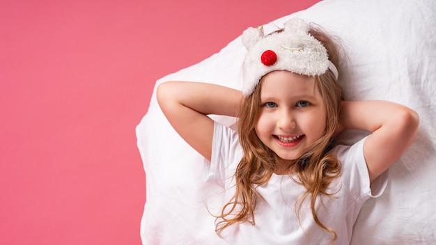 Petite Fille Dans Un Masque De Sommeil Est Allongée Sur Un Oreiller Avec Ses Mains Derrière Sa Tête Photo Premium