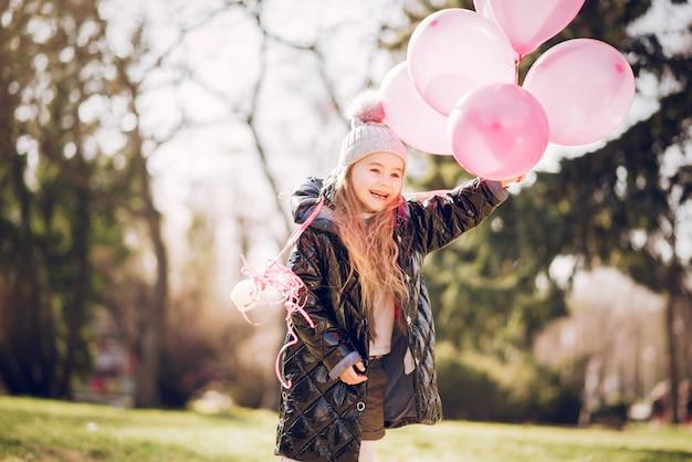 Petite fille dans un parc jouant sur l'herbe Photo gratuit