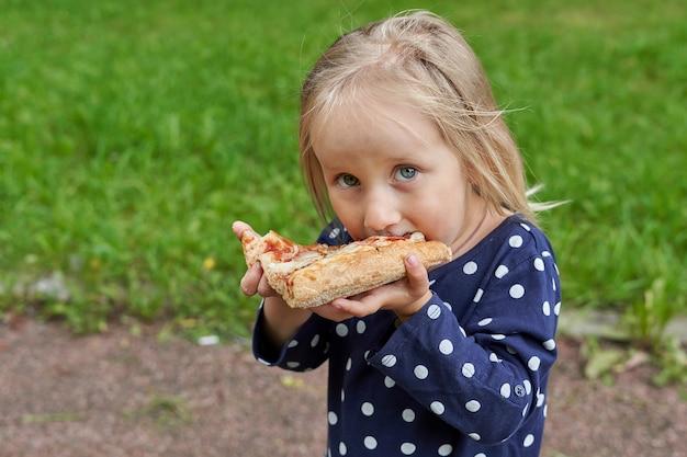Petite Fille Dans Une Robe Bleue à Pois Blancs Mangeant Une Grosse Tranche De Pizza Sur Fond D'herbe Verte Photo Premium