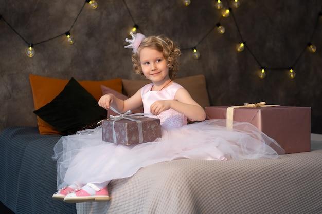 Une Petite Fille Dans Une Robe Rose Et Une Couronne Sur Le Lit Avec Des Cadeaux. Photo Premium
