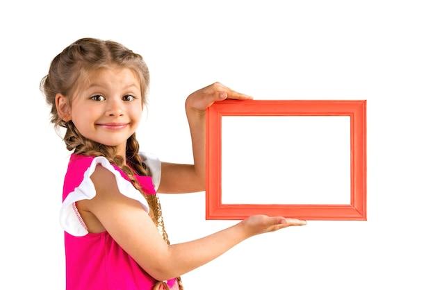 Une Petite Fille Dans Une Robe Rose Tient Un Cadre Photo. Photo Premium