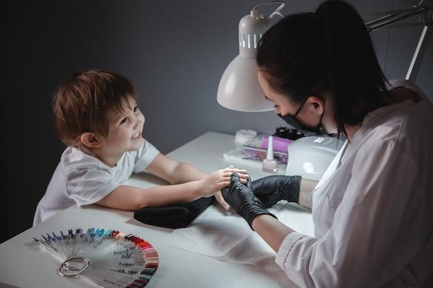 Une petite fille dans un salon de beauté. regarde le manucure dans un masque noir et des gants noirs. soins des ongles de l'enfant. Photo Premium