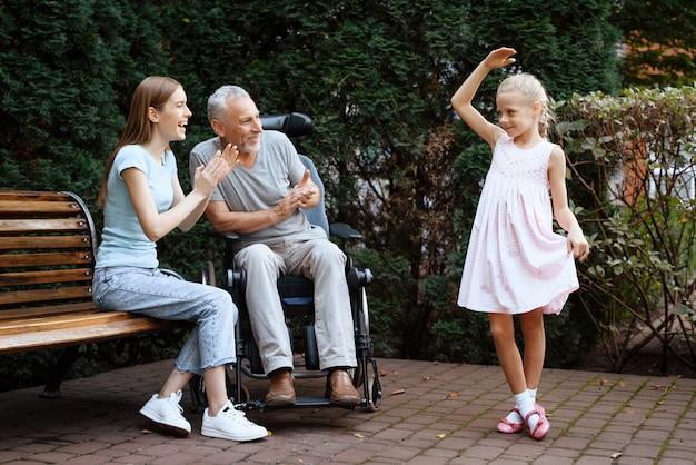 Petite fille danse, vieil homme et femme sourient Photo Premium