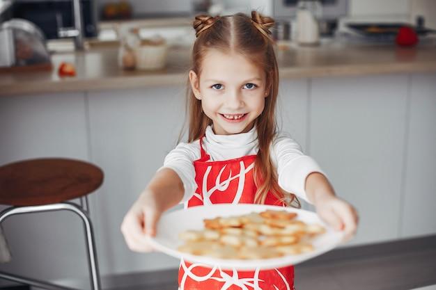 Petite fille debout dans une cuisine avec des cookies Photo gratuit