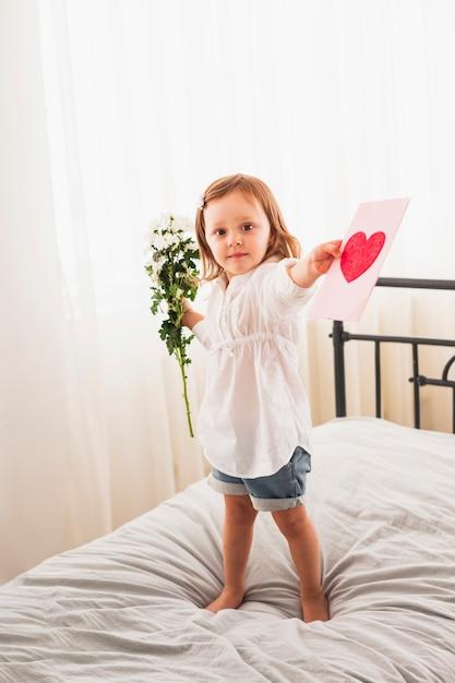 Petite fille debout avec des fleurs et carte de voeux Photo gratuit