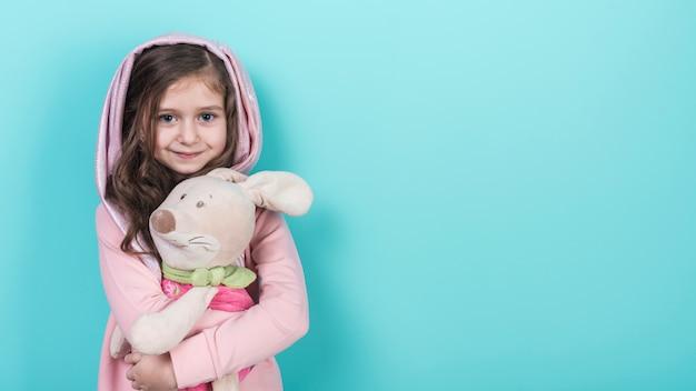 Petite fille debout avec jouet lapin Photo gratuit