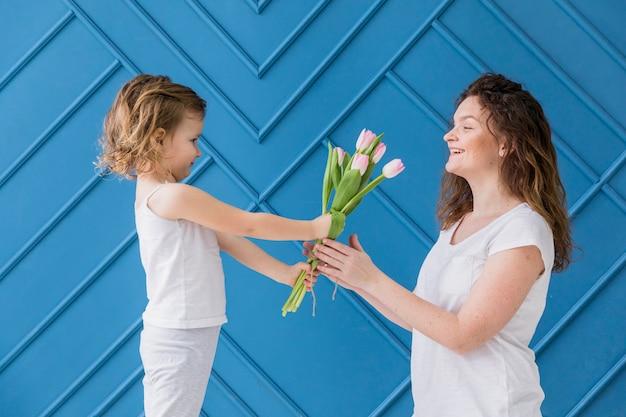 Petite fille donnant des fleurs de tulipes roses à sa mère le jour de la mère devant fond bleu Photo gratuit