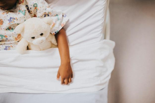 Petite fille dormant dans un lit d'hôpital Photo gratuit
