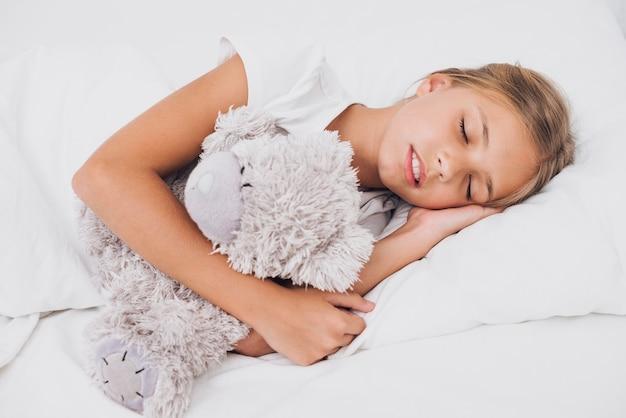 Petite fille dort avec son ours en peluche Photo gratuit