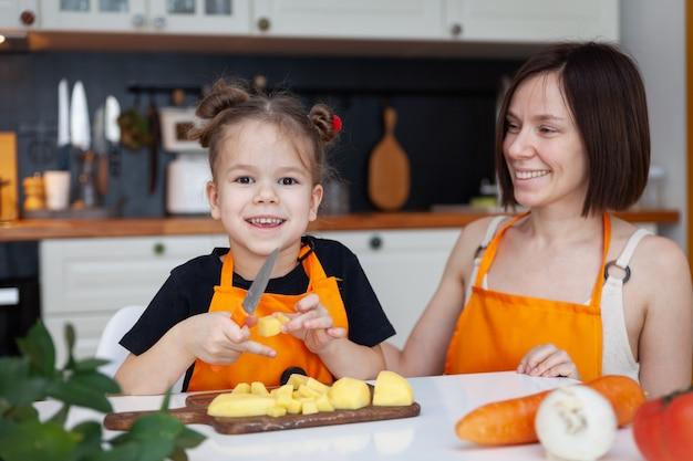 Petite Fille Drôle Et Belle Maman En Tablier Orange Cuisinent, Coupent, Hachent Des Légumes, Sourient. Photo Premium