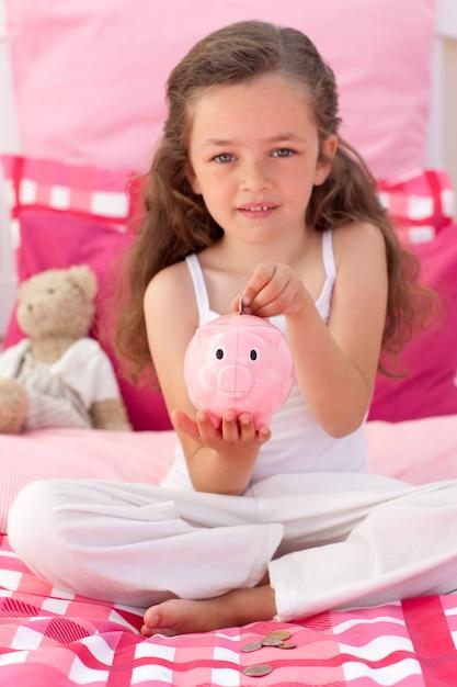 Petite fille, économiser de l'argent dans une tirelire Photo Premium