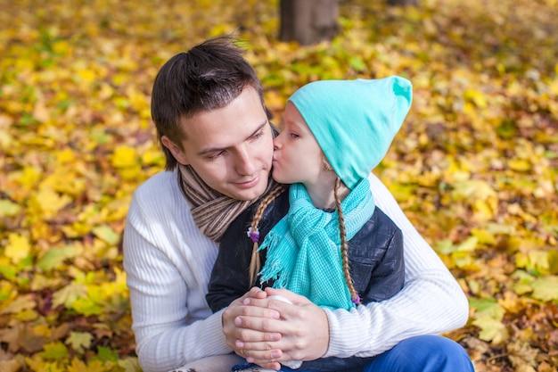 Petite fille embrasser père heureux en automne parc en plein air Photo Premium