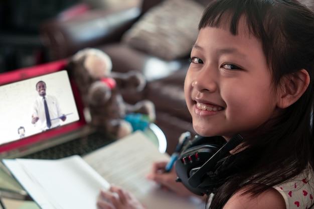 Petite Fille Enfant Apprentissage Sur Ordinateur Portable à La Maison, Distance Sociale Pendant La Quarantaine, Concept D'éducation En Ligne Photo Premium