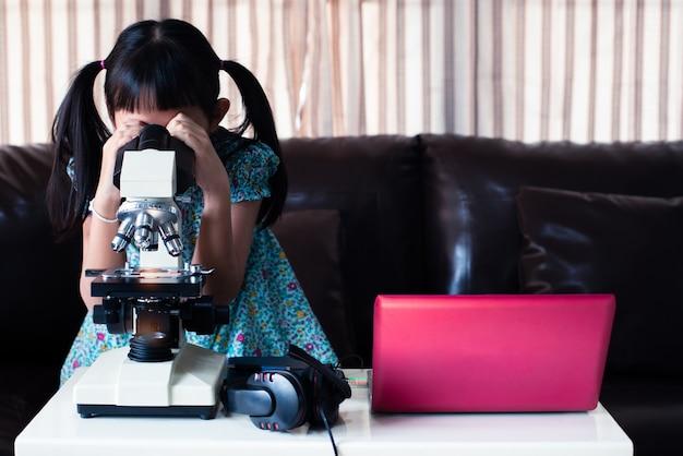 Petite Fille Enfant Asiatique à La Recherche De Microscope Et D'apprentissage En Ligne En Utilisant Un Ordinateur Portable Et à La Maison, L'enseignement à Distance Photo Premium
