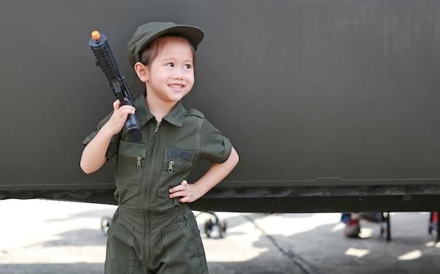 Petite fille enfant en costume de soldat pilote costume avec la tenue de pistolet à la main Photo Premium