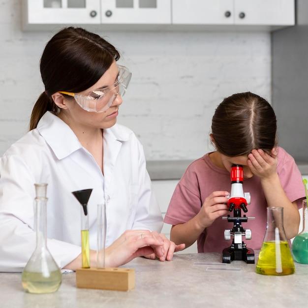 Petite Fille Et Enseignante Faisant Des Expériences Scientifiques Au Microscope Photo gratuit