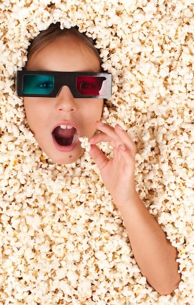 Petite fille enterrée dans le pop-corn avec des lunettes 3d Photo Premium