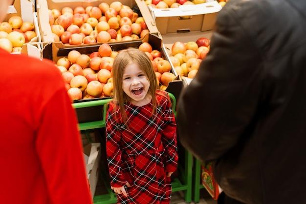 Une Petite Fille D'environ 5 Ans A Fait Une Crise De Colère Dans Un Supermarché Devant Ses Parents. L'enfant Crie Et Pleure, Suppliant Les Bonbons De Maman Et Papa Photo Premium