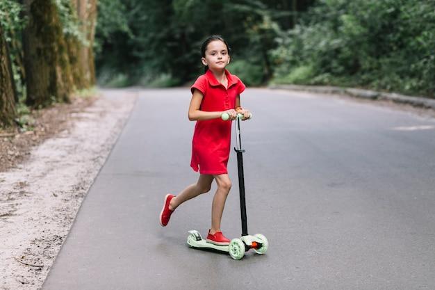 Petite fille, équitation, pousser, scooter, sur, route Photo gratuit