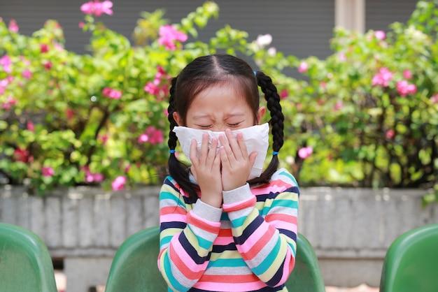 Petite fille éternue sur le nez avec du papier de soie en plein air Photo Premium