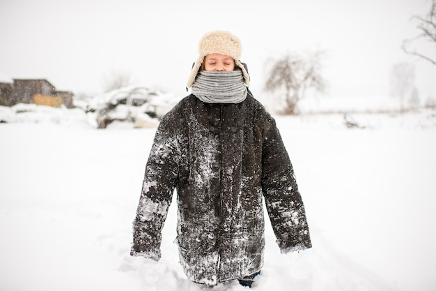 Petite Fille étrange Dans Des Vêtements Surdimensionnés, Debout Sur La Route Enneigée En Journée D'hiver Dans Le Village Russe Photo Premium
