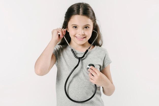 Petite fille explorant le rythme cardiaque avec stéthoscope Photo gratuit