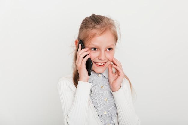 Petite fille faisant un appel téléphonique Photo gratuit