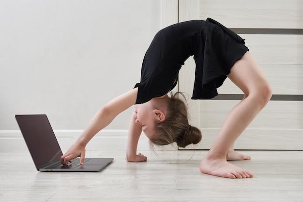 Petite Fille Faisant Des Exercices De Gymnastique à La Maison En Utilisant L'apprentissage En Ligne Avec Un Ordinateur Portable, Concept D'éducation Sur Internet Photo Premium