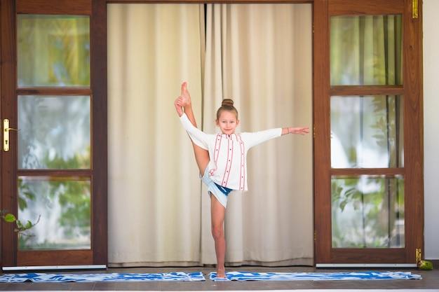 Petite fille faisant des exercices de yoga en plein air sur la terrasse Photo Premium
