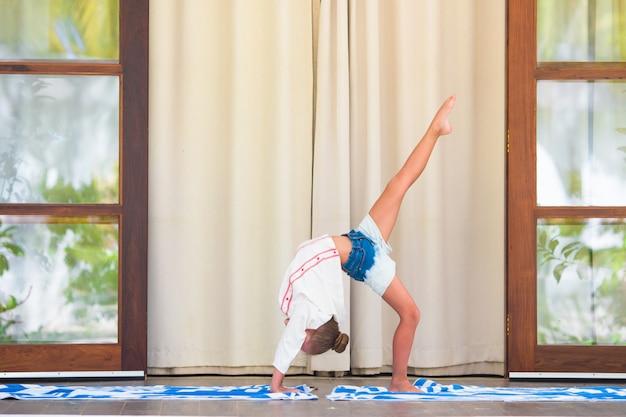 Petite fille faisant des exercices de yoga sur la terrasse en plein air Photo Premium