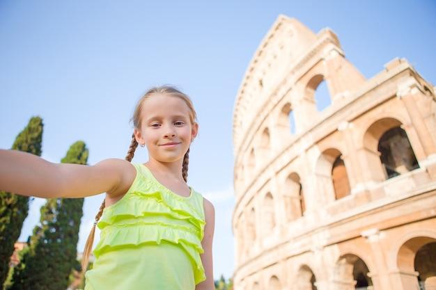 Petite fille faisant selfie fond colisée, rome, italie. portrait d'enfant dans des lieux célèbres d'europe Photo Premium