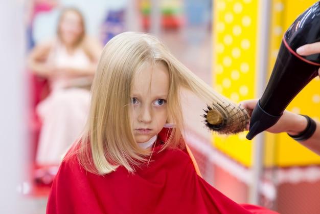 Une petite fille fait une coupe de cheveux chez le coiffeur. Photo Premium