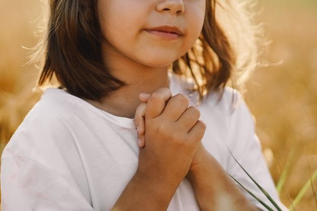 Petite Fille Ferma Les Yeux, Priant Dans Un Champ De Blé. Les Mains Jointes En Prière. Concept De Religion Photo Premium