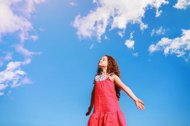La petite fille ferma les yeux et respira l'air frais du parc. Photo Premium
