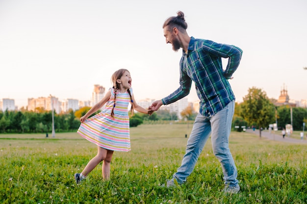 Petite fille fille enfant tenant la main de son père dans le parc Photo Premium