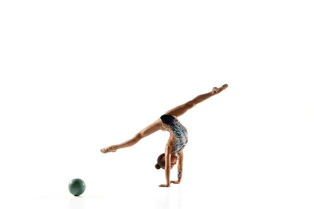Petite Fille Flexible Isolée Sur Un Mur Blanc. Petit Modèle Féminin En Tant Qu'artiste De Gymnastique Rythmique En Justaucorps Brillant. Grâce En Mouvement, En Action Et En Sport. Faire Des Exercices Avec Le Ballon. Photo gratuit
