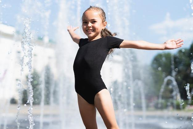 Petite fille avec une fontaine d'eau derrière Photo gratuit