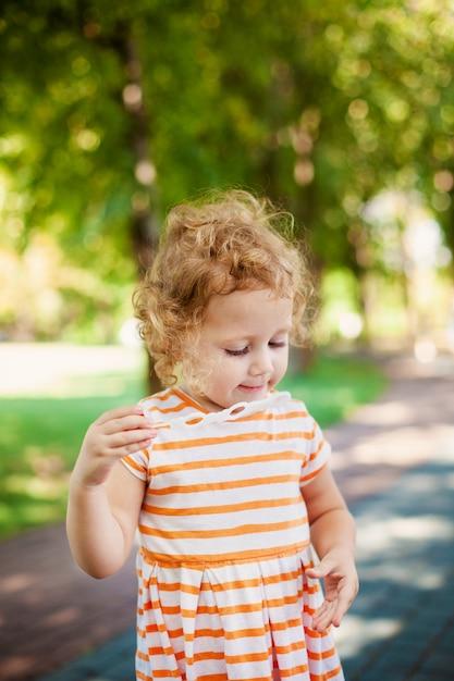 Petite fille frisée blonde soufflant des bulles de savon dans le parc de l'été Photo Premium