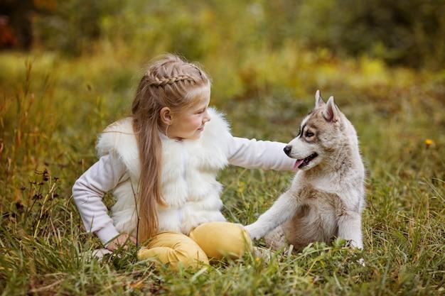 Petite fille frisée est assis dans la forêt d'automne avec des chiots husky Photo Premium